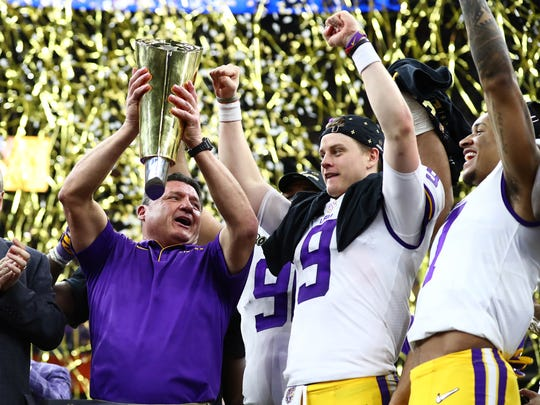 Jan 13, 2020; New Orleans, Louisiana, USA; LSU Tigers head coach Ed Orgeron hoists the national championship trophy with quarterback Joe Burrow after a victory against the Clemson Tigers in the College Football Playoff national championship game at Mercedes-Benz Superdome. Mandatory Credit: Matthew Emmons-USA TODAY Sports