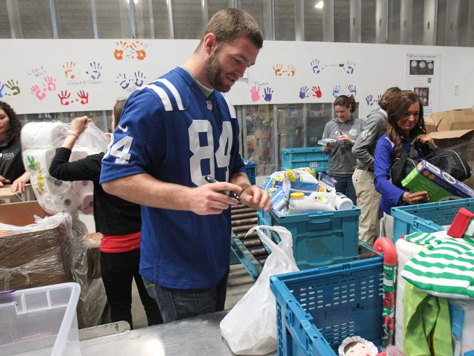 Jack Doyle, a tight end for the Indianapolis Colts, works on preparing items at the second annual Mayors Day of Recognition for National Service, at Gleaners Food Bank, Tuesday, April 1, 2014.  About 150 volunteers helped with prepping products and creating over 1,000 backsacks (cq.), which are food bags going to needy kids to provide non-perishable meals on weekends. The event, attracting thousands of volunteers, is recognized nationwide.