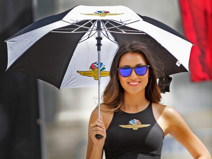 Indy Girl Cecilia Hernandez smiles as she takes to the shade of an umbrella during the IMS Pep Rally on Monument Circle, Wednesday, May 7, 2014.