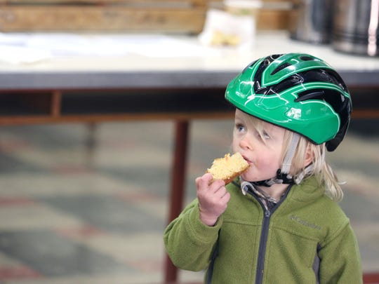 """Oaken Roden, 2, enjoys some sweet bread from Azteca bakery prior to participating (with his family) in The Northwest Hub's Cranksgiving, a race/scavenger hunt that collects food for the Marion-Polk Food Share, Saturday, Nov. 21, 2015, in Salem, Ore. Organizers call it a """"food drive on two wheels."""""""