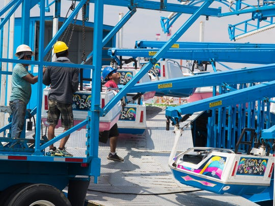 Crews with Wade Shows, Inc. assemble rides before the