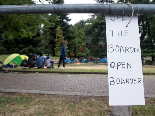 A sign reading 'open the boarder' is attached to a
