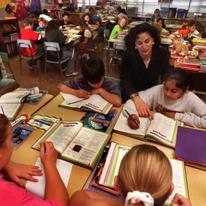 A fifth-grade teacher works with her students.