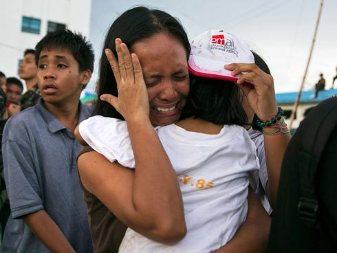 A woman carrying a child cries as other survivors of Typhoon Haiyan wait to board a C130 aircraft during the evacuation of hundreds of survivors on Nov. 13.