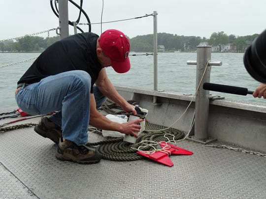 Justin Chaffin, senior researcher and research coordinator for Stone Lab and Ohio State University's Ohio Sea Grant College Program, gathers a water sample taken from Lake Erie near Gibraltar Island.
