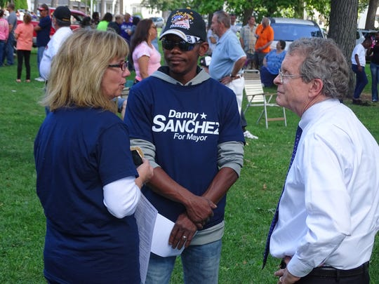 """Attorney General Mike DeWine speaks to Fremont residents Debra and Billy Benson on Sunday at the """"Mingle in the Park"""" event. DeWine publicly endorsed Republican Danny Sanchez for mayor at the event."""