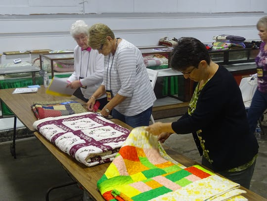 Linda Miller, right, of Uniontown, Ohio, judges quilts
