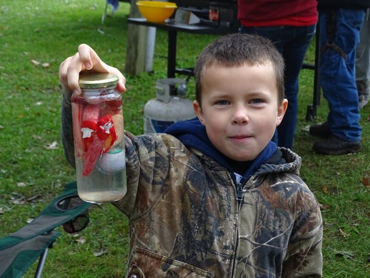 Logan Klavinger shows off a hand inside a jar as part of his family's spooky Halloween RV decoration.
