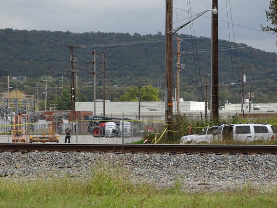 Police crime scene tape stretches nearly to the rail road tracks from North Brownell Street.