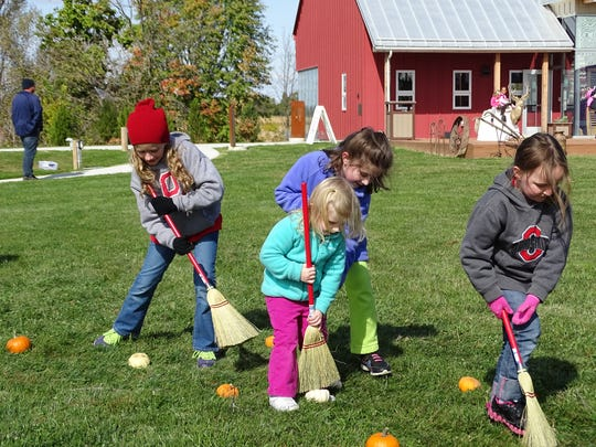 Reese Smith, 8,  left; Leah Wasserman, 7; Rachel Wasserman, 3;  and Ryla Smith, 5, all of Fremont, take part in a pumpkin roll activity Sunday at the Sandusky County Park District's Farm Days in Lindsey. This was the first year the park district had held the event at its new nature center.