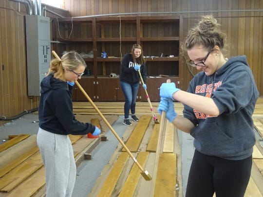 Ridgewood High School seniors Paige Patterson, Brittany Bradford and Holly McCoy, from left, seal wood that will be used to build a stage at the artPARK, set to open in May downtown. All three are members of Students Taking Action Through Service, who volunteered to work during Saturday's Make A Difference Day.