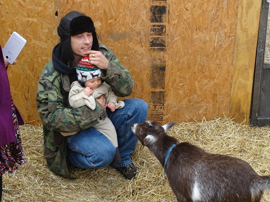 James Prebula Jr. holds his son, Dean, they visit with goats at Doebel's Flowers' petting zoo Sunday. The petting zoo was part of the Winesburg Weekend schedule of events.