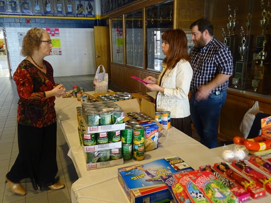 Event organizer Robin Hindall, left works with friends Aaron and Michelle Marks to collect donations during the Community Thanksgiving Meal at Woodmore High School.