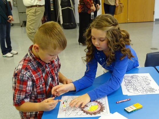 Ainsley Chovan, 10, helps Max Perkins, 5, to color at the kids table during the community meal.