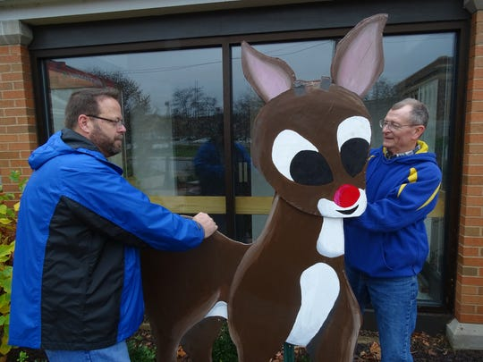 Dana Matz, left, director of member services with the chamber, puts the finishing touches on decorations outside the visitor's bureau downtown. The Rudolph statuette was made by students at MidEast Career and Technology Center.