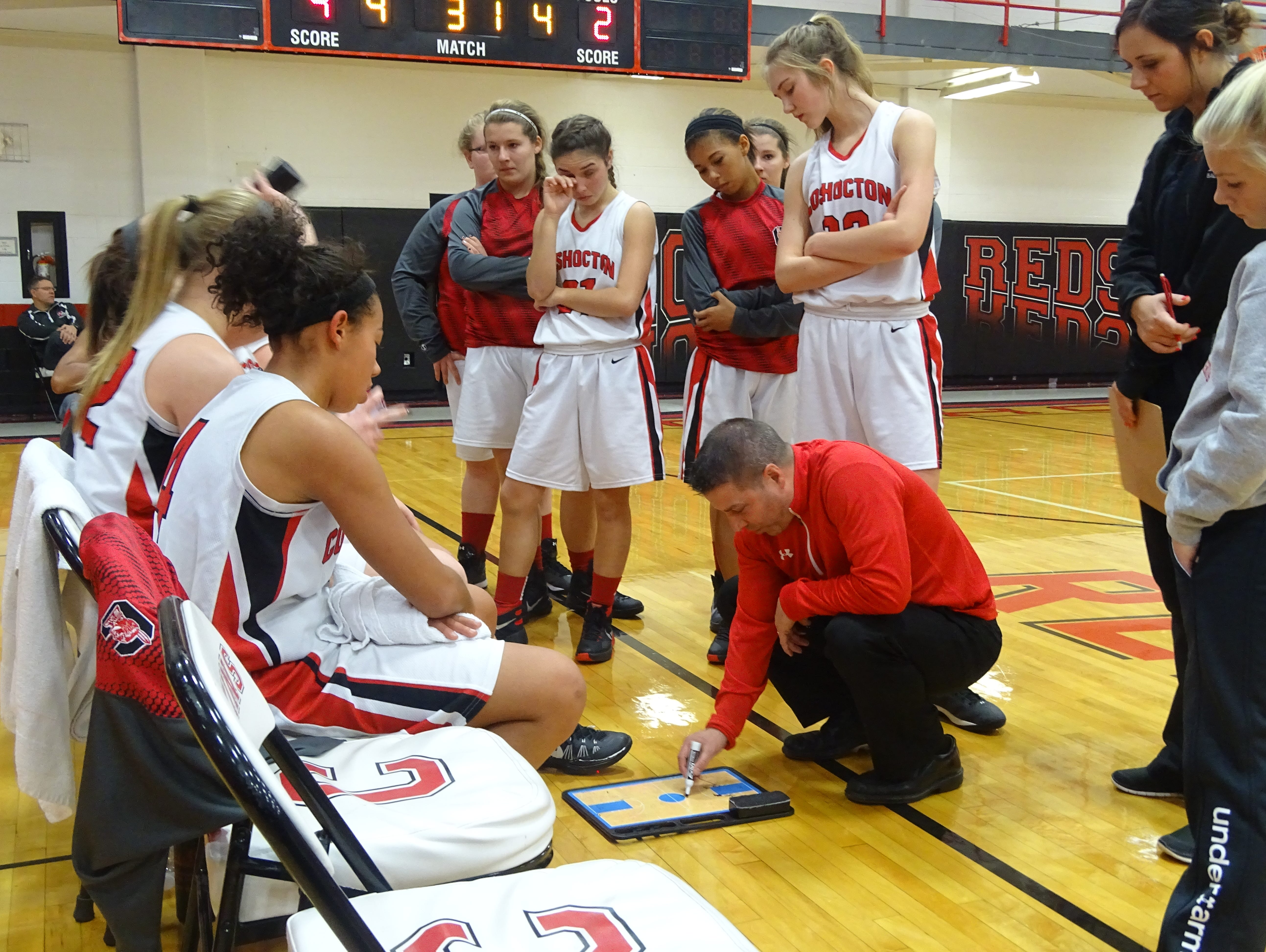 Coshocton coac h Paul Bowman goes over a play with his team during a timeout Saturday.