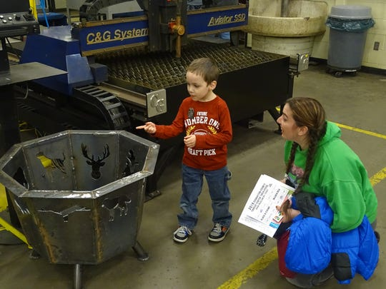 Perry Brown, 4, of Coshocton, identifies animal shapes in a fire pit made by Coshocton County Career Center students to his mother, Tiffany Brown. The Browns visited career tech labs during Thursday's annual open house at the school .
