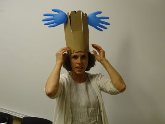 Anne Cornell, artistic director of the Pomerene Center for the Arts, made this hat Wednesday to demonstrate family art-making at the center.