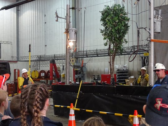 AEP workers demonstrate what can happen when a tree falls on a power line for students from Keene Elementary School Wednesday.