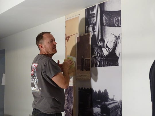 Jeremy Middleton of Wrap Ratz puts up a wall covering at the Rutherford B. Hayes Presidential Library & Museums on Monday. The facility will celebrate its Centennial Celebration May 28 to 30.