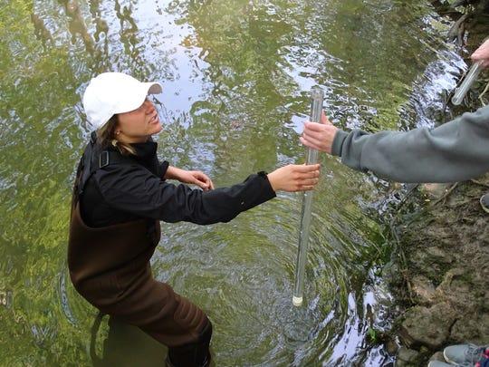 Kaylie Darayman, a volunteer coordinator for Black Swamp Conservancy, tests water from Muskellunge Creek.