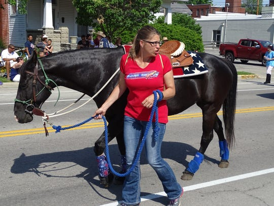 Kimberly Smith walks with her horse, Annie, as part of Fremont Baptist Temple's Cowboy Camp contingent in the annual Memorial Day parade.