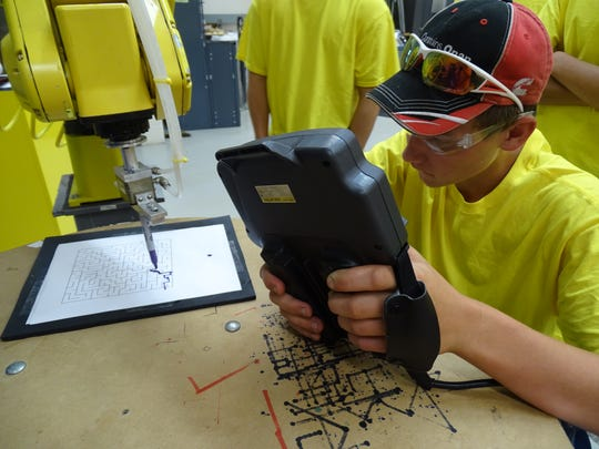 Payton Buhrow, 16, of Woodmore High School uses a marker attached to a robot to draw lines through a maze. This technique is one of the first lessons learned by students in the robotics program at Terra State Community College.