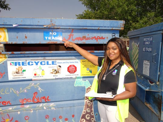 "SCSWA recycling coordinator Tarkeysha Burton points to the ""NO TRASH"" signage on the front of the blue recycling bin."