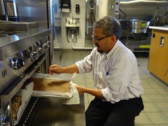 John Bermudez checks on brownies Tuesday at Terra State Community College's culinary lab. Bermudez will run the college's dining services under a new reorganization plan. Holly Hoffman will be manager of conference and event services.