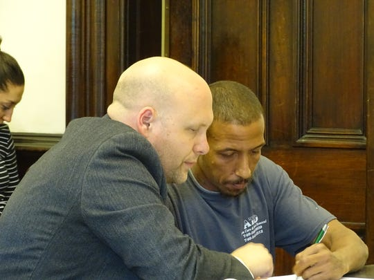 Jason Norfleet, of Coshocton, signs a guilty plea in court Friday while defense attorney Dan Guinn looks on. Norfleet pleaded guilty to kidnapping and aggravated burglary charges in a Feb. 3 home invasion on Vine Street.