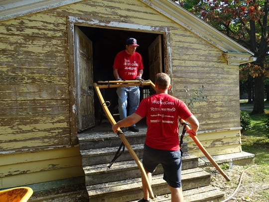 Sam Renfroe of North Central State College and Tasos Papachristoudis of OhioHealth help clear a storage room at Raemelton Therapeutic Equestrian Center during United Way of Richland County's Day of Caring Friday.