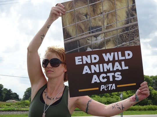Jennifer O'Brien of Bellevue holds up a sign Tuesday at a protest against the Kelly Miller Circus. The circus held two events in Bellevue Tuesday night, with about 40 protesters speaking out against what they described as the circus' mistreatment of its animal acts.