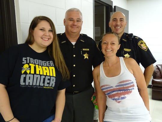 Taylor Wamsley, left and Michelle Ickes, right, post with Sandusky County Jail Captain Mark Fisher, left, and Sandusky County Sheriff Capt. Jamison Rose.