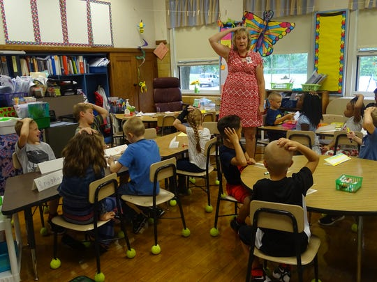 First grade teacher Jennifer Jarvis keeps her classroom quiet on the first day of school by asking students to place their hands on their heads.