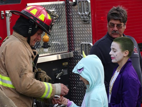 Port Clinton firefighter engineer Dave Koebel hands out candy to trick-or-treaters at the corner of Alice and Taft Streets Monday night.
