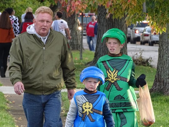Ron Dowling, pictured left, walks with his sons Thomas Dowling, 6, and Gavin Dowling, 11 of Port Clinton Monday night as the family went trick-or-treating on Taft Street.