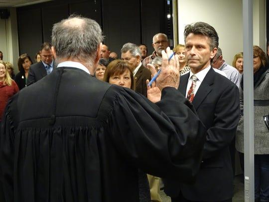 Scott Miller is sworn in by Sandusky County Common Pleas Court Judge John Dewey Thursday. Miller is one of two newly elected Sandusky County commissioners.