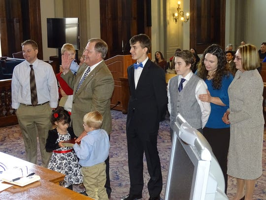 Ross County Treasurer Jerry Byers raises his right hand to take the oath of office while surrounded by his family in December 2016.
