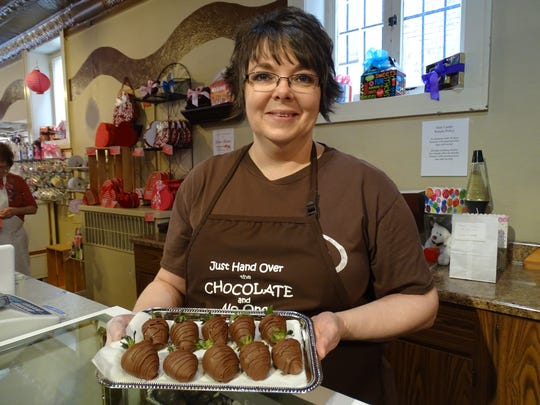 Coco Beans owner Donna McNemar holds a plate of strawberries covered in milk chocolate. All the chocolate is made at the downtown Fremont store, ensuring that every Valentine's Day gift is fresh.