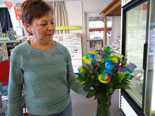 Otto Urban owner Lynn Urban shows off a bouquet of rainbow roses. The uniquely dyed roses are a popular gift offering a colorful spin on the traditional rose.