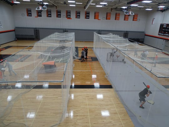 After Friday's rain out, Ridgewood baseball practices its hitting from inside the Ridgewood High School gymnasium.