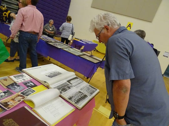 Bryian Hysell looks at old Bloom-Carroll sports photos at the district showcase Tuesday evening in the middle school gym.