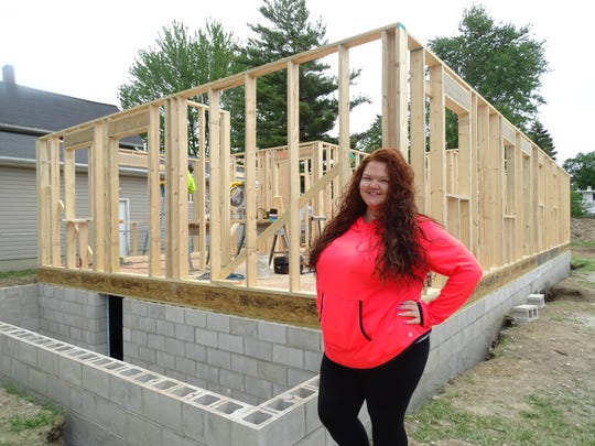 Mia Sorg, 20, of Clyde stands next to a home she will move into in the fall as part of Habitat for Humanity. Sorg is putting in sweat equity this week and will work 400 hours helping with the homes build.