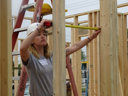 Sarah Caldwell, a 23-year-old AmeriCorps volunteer from Knoxville, Tennessee, takes measurements for a doorway in a Habitat for Humanity home at 151 South Buchanan St. in Fremont.
