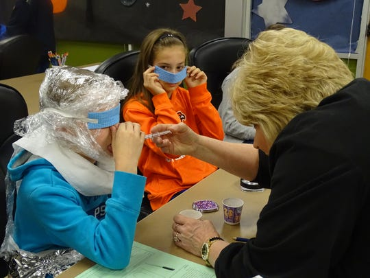 Students Parker Zelns, 11, Natalie Frye, 11 and Virginia DaBrunz, 11, are blindfolded and pinch their nose to simulate the lack of taste buds in zero gravity. Vanguard teacher Jenny McCoy administers the test with salty, sweet and sour tastes.