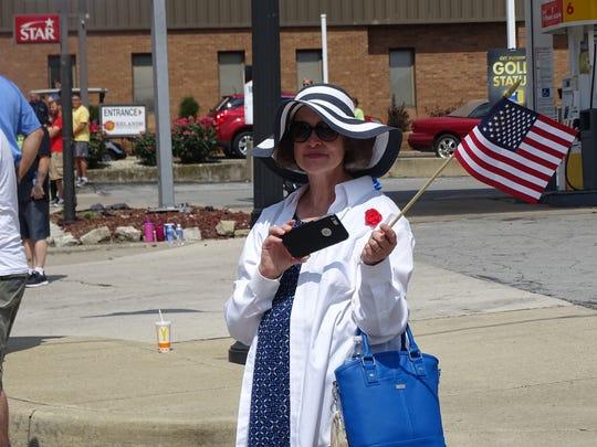 Cheryl Dendinger waves an American flag as the motorcade escorting the traveling Vietnam Memorial Wall travels through Bellevue.