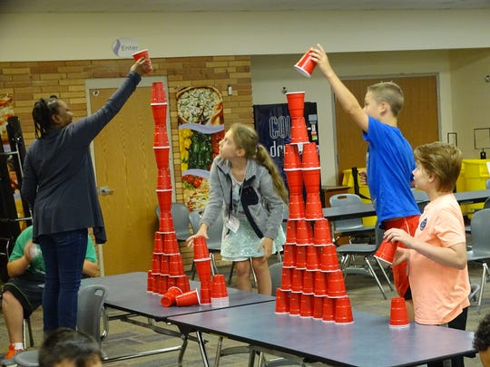 Participants in a manufacturing camp at Pickaway-Ross Career & Technology Center Wednesday race to see who can build the tallest cup tower using engineering principles they had learned.