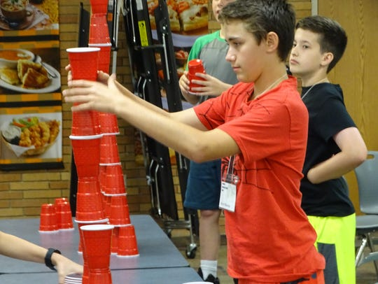 Bryce Blaney tries to keep his cup tower balanced in