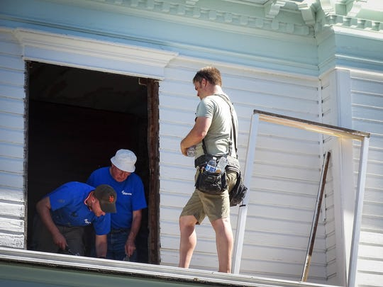 Tyler Butenschoen, Gordon Wilson and Mackenzie Strawn work to remove and replace a deteriorating window at the Brown House in Stayton as part of the iServe project.
