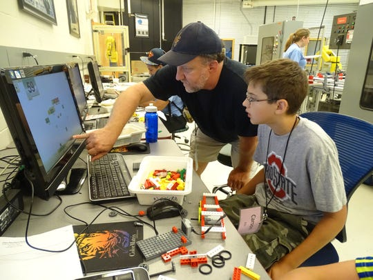 Instructor Dave Bradley works with 12-year-old Carson